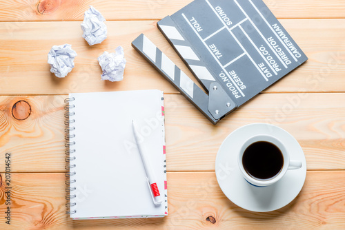 a notebook, a cup of coffee and a clapper for shooting movie episodes on wooden Fototapet