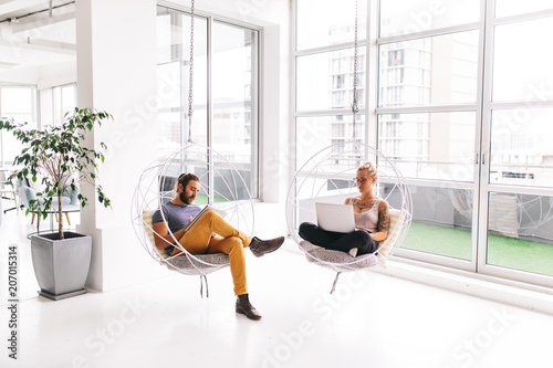Man and woman working next to each other in office