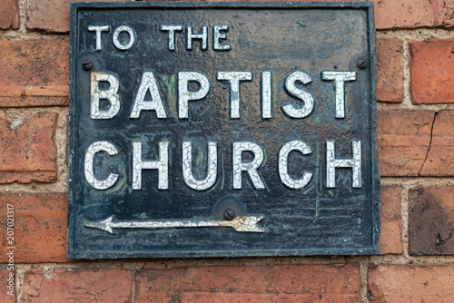 Canvas Print metal and enamel street sign on brick wall stating to the baptist church with ar