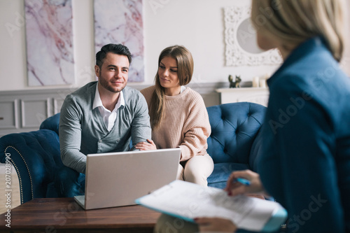 Obraz na plátně Happy couple planning their future while consulting with insurance agent in their home