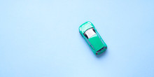 Green Toy Car On Abstract Blue Background. Travel, Purchase Minimal Concept