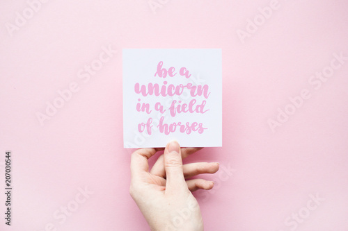 Minimal composition on a pink pastel background with girl's hand holding card wi Fototapet