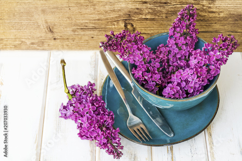 Keuken foto achterwand Lilac Spring Table Setting with Vintage Blue Cutlery and Lilac Flowers on a Marble Background.Floral Table Decor