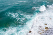 Big waves breaking on the shore. Waves and white foam. Coastal stones. View from above. The marine background is green