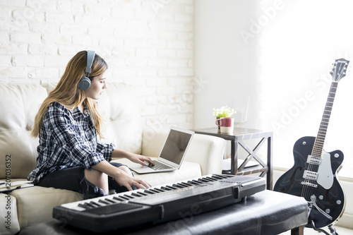 Female musician composing music at home - 207036352