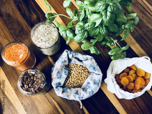 Healthy cereals and fruits in glass jars and reusable bags with fresh basil on wooden background in daylight