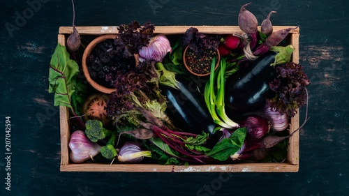 Poster Cuisine Purple food. Fresh vegetables and berries in a wooden box. On a wooden background. Top view. Copy space.