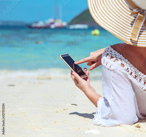 Tuinposter Artist KB Relaxed lady using a smartphone on a tropical beach