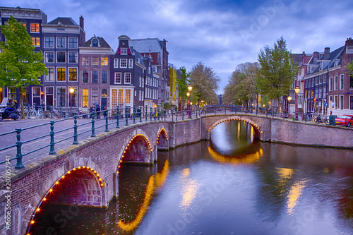 Plakat Widok z Amsterdamu pejzaż z jednym z jego kanałów. Oświetlony most i tradycyjne holenderskie domy o zmierzchu.
