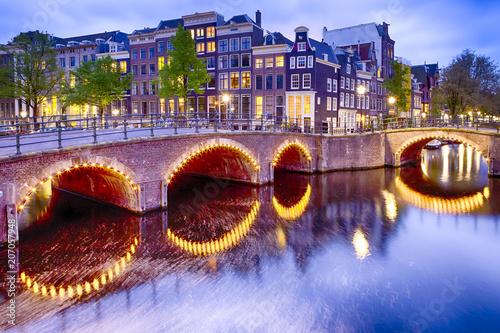 Plakat Koncepcje podróży. Nocny widok na panoramę Amterdam z jednym z jego kanałów. Oświetlony most i tradycyjne holenderskie domy o zmierzchu.