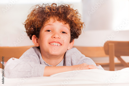Fotografija  Happy preteen boy sitting backwards on white sofa