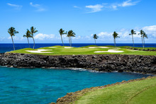 Sunny Day On A Tropical Golf Course Fairway With The Putting Green In The Distance Surrounded By Palm Trees And Sand Traps, Lava Rock, Blue Pacific Ocean, And Blue Sky And White Clouds In Background