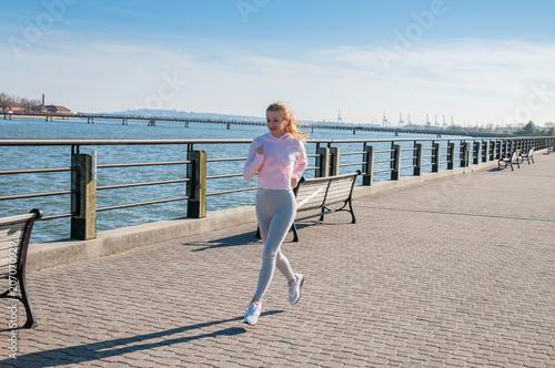 Woman in sportswear jogging on the quay near ocean. Wallpaper Mural