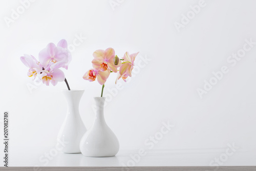 Foto auf Leinwand Blumen beautiful orchids in white vase on white table