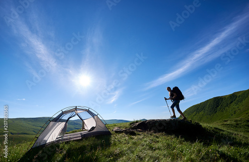 Fototapeta Young woman backpacker with backpack and trekking sticks climbing up on big stone on the top of a hill near tent against blue sky, sun and clouds, in the mountains. Camping lifestyle concept obraz