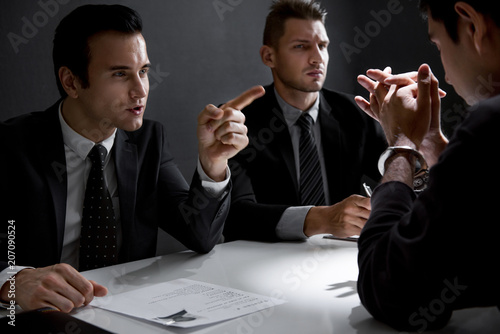 Foto  Criminal man with handcuffs being interviewed in interrogation room