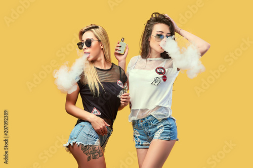 Valokuva  Side view of trendy young female in glasses and shorts standing and smoking on s
