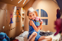 Charming Little Girl Having Fun In Cardboard Playhouse With Toys And Smiling At Camera.