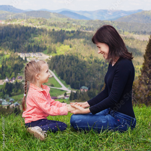 Photo  Mom and little daughter are sitting on top of the mountain