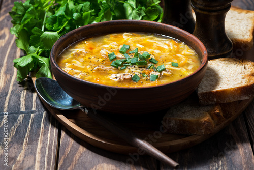 chicken soup with egg noodles in a bowl on wooden background