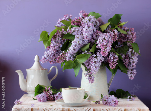 Foto op Canvas Lilac Blooming purple lilac in a jug, Cup and teapot. Still life in rustic style.