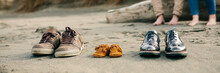 Family Shoes In The Sand With Pregnant Woman In The Background With Her Partner
