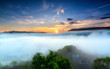 Dawn on plateau in morning with colorful sky, while sun rising from horizon shines down to small village covered with fog shrouded landscape so beautiful idyllic countryside Dalat plateau, Vietnam