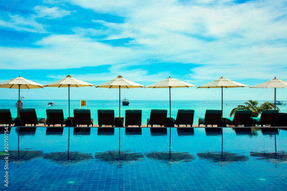 Fototapeta Beach resort umbrella reflect with sea