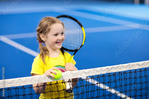 Child playing tennis on indoor court