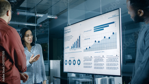 Photo  Beautiful Hispanic Woman Analyzes Statistics, Charts and Pies with Company's Growth Shown on a Wall TV