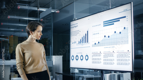 Fotografie, Obraz  Beautiful Caucasian Woman Analyzes Statistics, Charts and Pies with Company's Growth Shown on a Wall TV