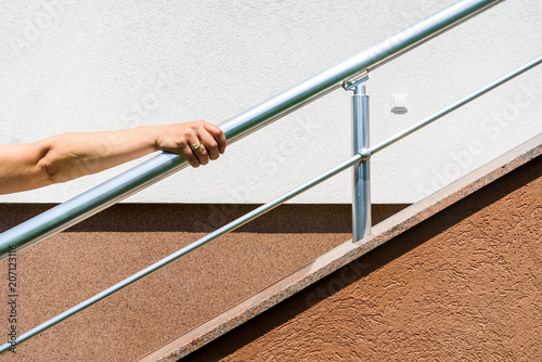 Valokuva  chrome fence on staircase. hand holds stainless steel fence