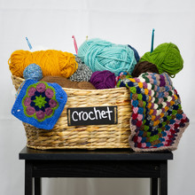 Basket Of Yarn With Crochet Hooks And Granny Squares