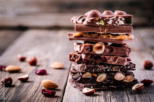 obraz dibond Stack of milk and dark chocolate with nuts, caramel and fruits and berries on wooden background.