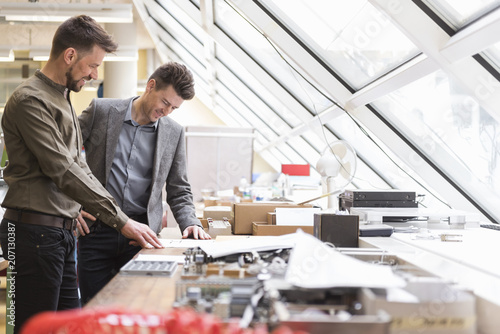 Two smiling businessmen looking at plan in factory