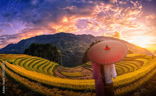 Foto auf Gartenposter Reisfelder Woman holding traditional red umbrella on Rice fields terraced with pine tree at sunset in Mu Cang Chai, YenBai, Vietnam.