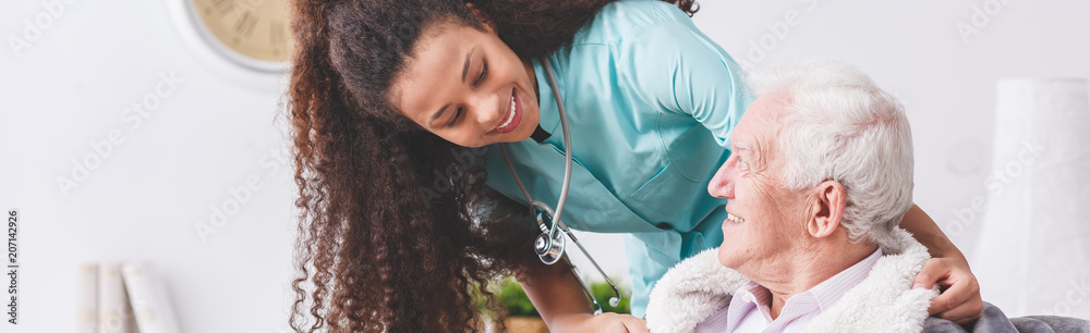 Fototapeta Panorama of a happy nurse with a stethoscope covering an elderly man with a blanket in a nursing home