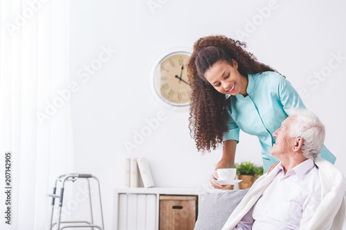 Fotografia  Young caregiver serving a cup of tea to a happy, older man in a retirement home