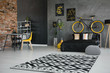 Leinwandbild Motiv Real photo of a teenager's bedroom interior with black bed, bike on the bedhead, yellow chair at desk and geometric rug