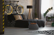 Leinwandbild Motiv Modern bedroom interior with decorative cushions on black bed, a bicycle on the bedhead and copper tray on gray pouf. Real photo