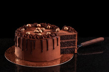 Chocolate Cake With Nuts On A Black Background