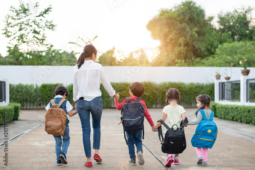 Valokuva  Group of preschool student and teacher holding hands and walking to home
