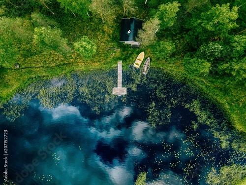 widok-z-lotu-ptaka-sauny-przy-brzegu-jeziora-drewniane-molo-z-lodzi-rybackich