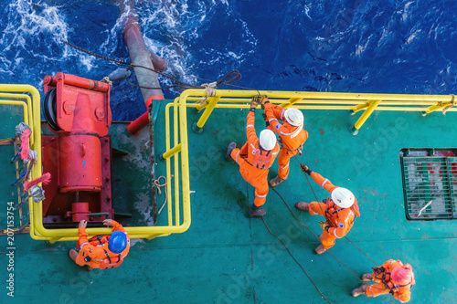 Offshore workers working together during anchor handling job on a construction barge at oil field