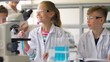 education, science and children concept - teacher and students with test tubes studying chemistry at school laboratory
