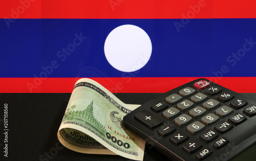 Poster Chicken One thousand of banknote currency Lao Kip with calculator on the black floor with Laos nation flag background. It is the money of Laos in 1999, and the concept of finance.