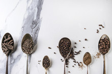 Variety Of Different Black Peppers Allspice, Pimento, Long Pepper, Monks Pepper, Peppercorns And Ground Powder In Vintage Spoons Over White Marble Texture Background. Top View, Space.