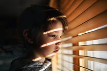 Boy Standing By A Window Looki...