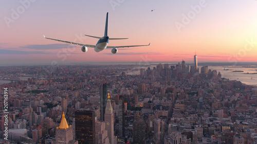 Fototapeta AERIAL: Passenger airplane flying over downtown Manhattan at beautiful sunset. obraz