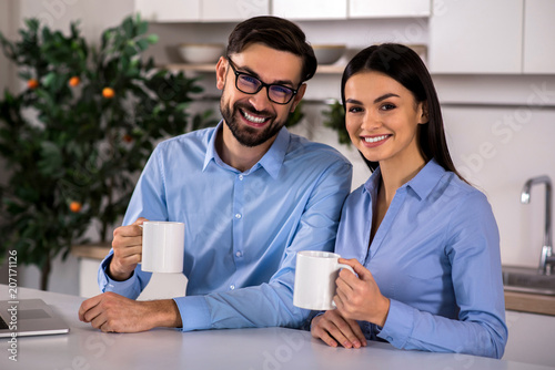 Fototapeta Positive couple drinking tea in the kitchen obraz na płótnie